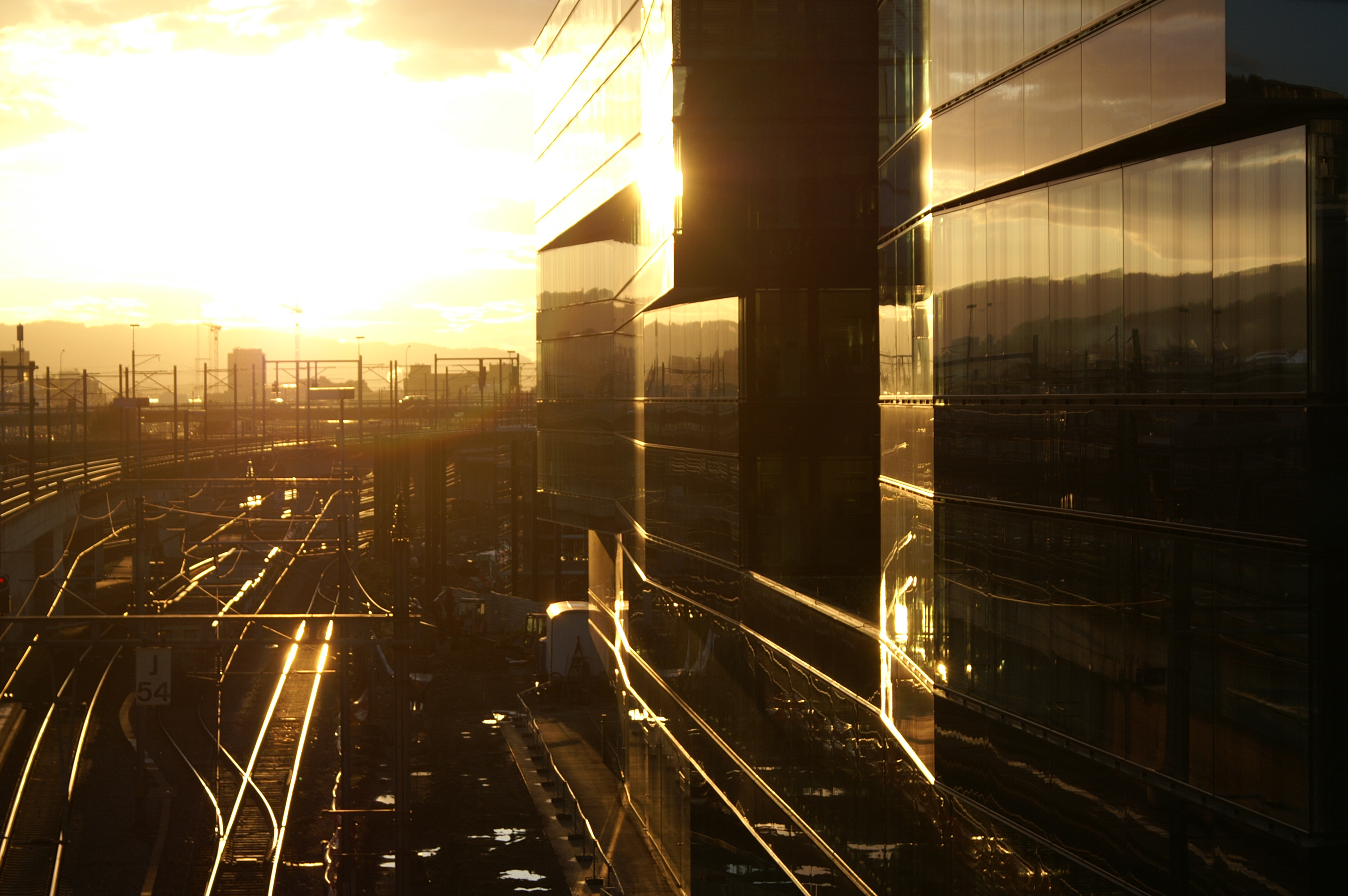 Ernst & Young Office Building next to Hardbruecke Train Station Tracks at Sunset